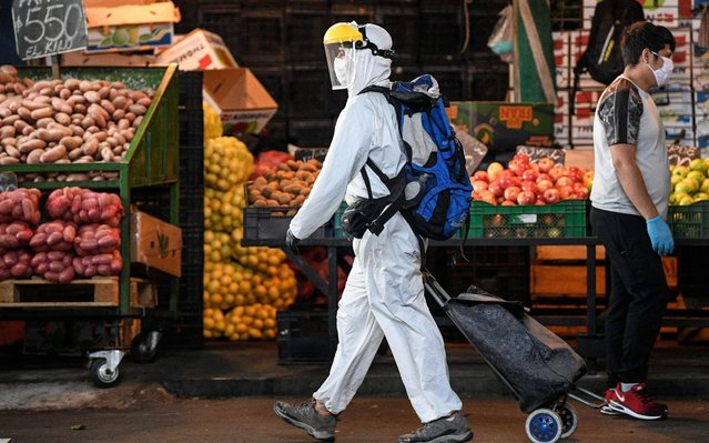 A citizen wearing protective suit shops at a market in Santiago, Chile, April 16, 2020 Chile has taken stringent measures to contain the virus, including imposing a night time curfew, suspending classes, closing non-essential businesses, and mandating the use of face masks on all public transit. (Photo by Jorge Villegas/Xinhua News Agency)