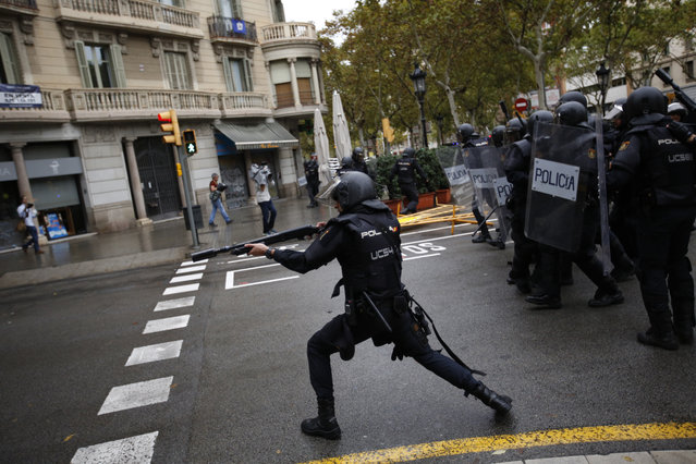Spanish riot police shoots rubber bullet straight to people trying to reach a voting site at a school assigned to be a polling station by the Catalan government in Barcelona, Spain, Sunday, October 1, 2017. Spanish riot police have forcefully removed a few hundred would-be voters from several polling stations in Barcelona. (Photo by Emilio Morenatti/AP Photo)