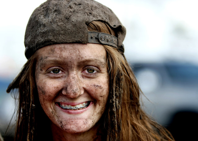 The mud covering her hat, hair and face can't cover the smile of Casey Walls, 17, of Port St. Lucie. (Photo by Gary Coronado/The Palm Beach Post)