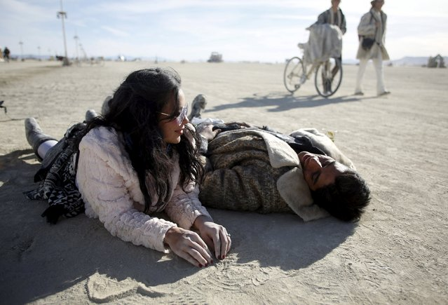 "Astrid Perez (L) and Ramon Camacho lay on the Playa during the Burning Man 2015 ""Carnival of Mirrors"" arts and music festival in the Black Rock Desert of Nevada, September 6, 2015. Sunday marks the last day of the sold-out festival that gathered approximately 70,000 people from all over the world. (Photo by Jim Urquhart/Reuters)"