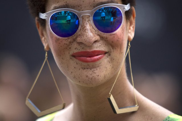 A fashionista wearing sunglasses smiles as she walks around Lincoln Center during New York Fashion Week in the Manhattan borough of New York September 6, 2014. (Photo by Carlo Allegri/Reuters)