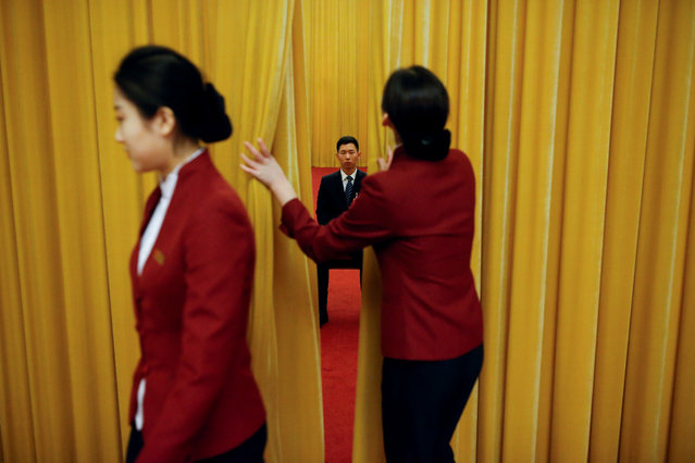 A security officer keeps watch behind a curtain on the second day of the 19th National Congress of the Communist Party of China at the Great Hall of the People in Beijing, China on October 19, 2017. (Photo by Thomas Peter/Reuters)
