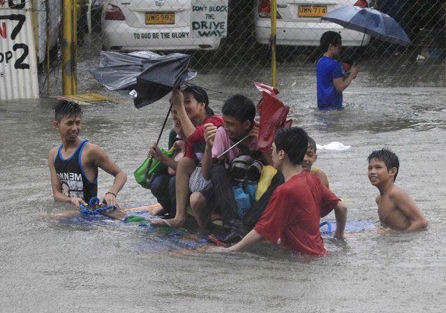 Stranded passengers ride on improvised wooden floaters to cross a flooded street after tropical storm Fung-Wong battered metro Manila September 19, 2014. (Photo by Erik De Castro/Reuters)