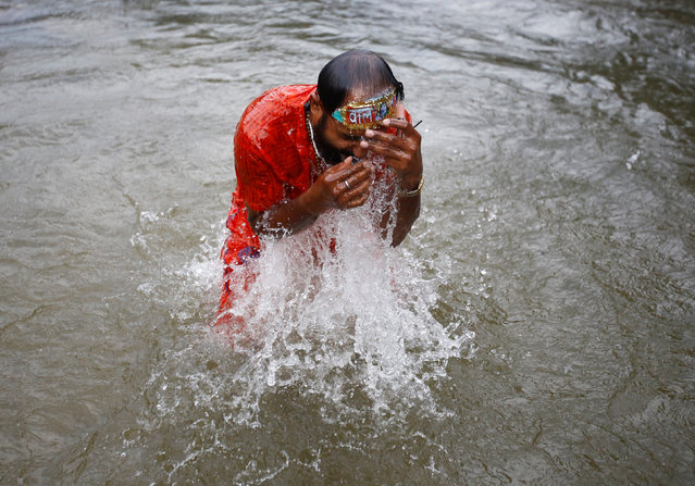 "A devotee takes a holy dip at the Bagmati River while participating in the ""Bol Bom"" (Say Shiva) pilgrimage in Kathmandu, Nepal, August 8, 2016. (Photo by Navesh Chitrakar/Reuters)"