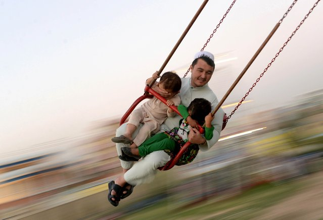 In  this photograph taken on September 12, 2014 an Afghan man and his children enjoy a ride on the swings at a park in Mazar-i- Sharif. Afghanistan's economy has improved significantly since the fall of the Taliban regime in 2001 largely because of the infusion of international assistance. Despite significant improvement in the last decade the country is still extremely poor and remains highly dependent on foreign aid. (Photo by Farshad Usyan/AFP Photo)