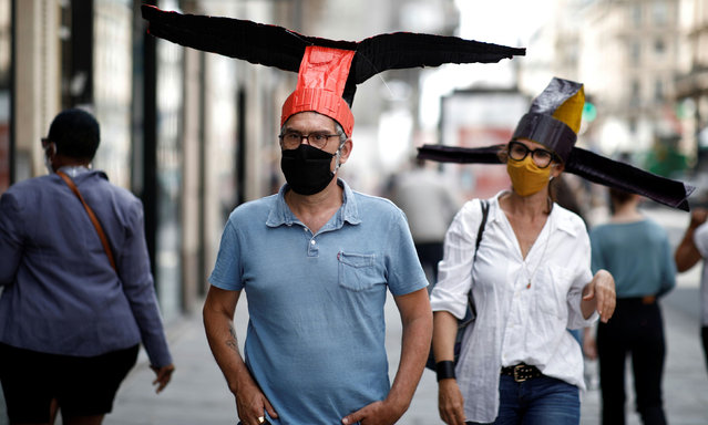 "Artists wear colourful ""deconfinement hats"" made of paper mache and inspired by Song dynasty headwear, for social distancing, at 59 Rivoli gallery in Paris as it prepares a general reopening later in the week, following the outbreak of the coronavirus disease (COVID-19) in France, June 3, 2020. (Photo by Benoit Tessier/Reuters)"