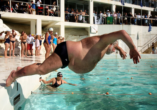 """A member of Icebergs Swimming Club dives in to the pool during the opening day of the winter swimming season at Bondi Icebergs on May 4, 2008 in Sydney, Australia. Bondi Icebergs, which began in 1929, is known as the """"Home of Winter Swimming"""", and has in excess of 700 dedicated swimmers competing in handicapped races during the winter season, lasting from the first weekend in May to the last weekend in September. The first Sunday in May each year is the official opening of the winter swimming season and members jump in to the pool with blocks of ice. (Photo by Ezra Shaw)"""