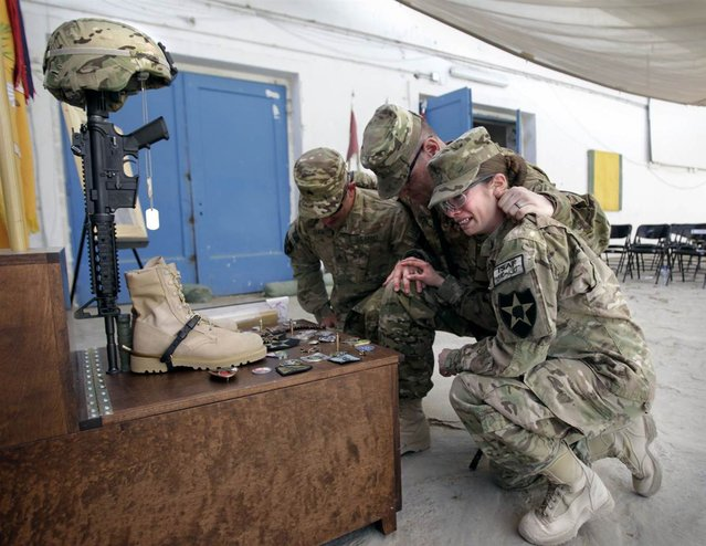 Spc. Katie Luna of 572nd Military Intelligence Company, 8th Squadron, 1st Cavalry Regiment cries while paying respects during a memorial service for platoon member Spc. Brittany Gordon, at Camp Nathan Smith in Kandahar province, southern Afghanistan, on October 19, 2012. Gordon was killed Oct. 13 along with another U.S. civilian and two others, after an Afghan police officer exploded a suicide vest he was wearing, a military officer said. (Photo by Erik De Castro/Reuters)