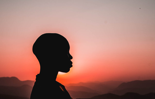 """""""Hope on the Horizon"""". A young Swazi girl holds on to the hope found in Jesus Christ promised to her daily in the sunset over the mountains. Photo location: Mbabane, Swaziland, Africa. (Photo and caption by Christina Kehres/National Geographic Photo Contest)"""
