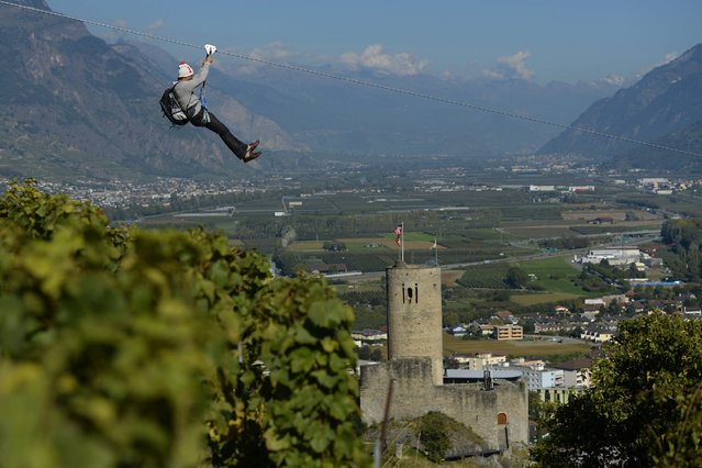 "A man slips down the zipline before the opening of the fair ""Foire du Valais"" above the town of Martigny, Switzerland, 02 October 2014. The Zipline is made of 1'123 meters of cable; it takes one minute 10 to slip down, passes an altitude of 120 meters and a speeds of up to 85 km. According the organizer of the fair the Zipline driving through a town of 18,000 inhabitants, should be unique in the world. (Photo by Maxime Schmid/EPA)"