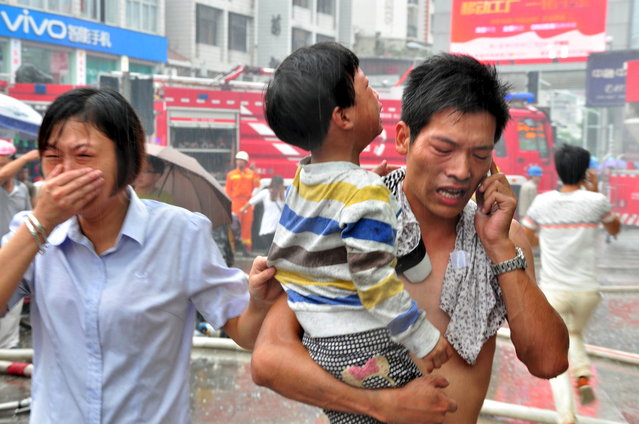 A man holds a child after rescuing him from a kindergarten affected by a fire at a commercial building, in Ningde, Fujian province, China, September 16, 2015. According to local media, more than 260 people were evacuated due to the fire, which broke out Wednesday morning. No causalities have been reported and the cause of it is still unknown. (Photo by Reuters/China Daily)