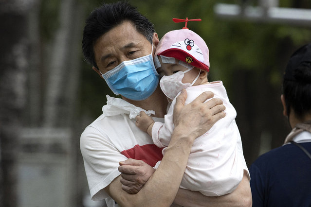 A man holds a child wearing masks to curb the spread of the coronavirus in Beijing on Wednesday, June 17, 2020. (Photo by Ng Han Guan/AP Photo)