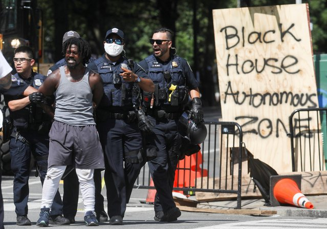 Washington, D.C. Metropolitan Police officers detain a man as they clear the entire area around Black Lives Matter Plaza during racial inequality protests near the White House in Washington, U.S., June 23, 2020. (Photo by Leah Millis/Reuters)