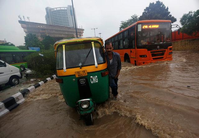 A man pushes his auto rickshaw through a flooded street during heavy rains in New Delhi, India, August 29, 2016. (Photo by Adnan Abidi/Reuters)
