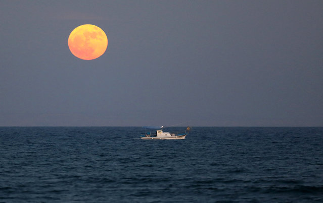 "A fishing boat sails as so-called ""Supermoon"" rises in Larnaca, Cyprus, 03 December 2017. (Photo by Christo Doulou/EPA/EFE/Rex Features/Shutterstock)"