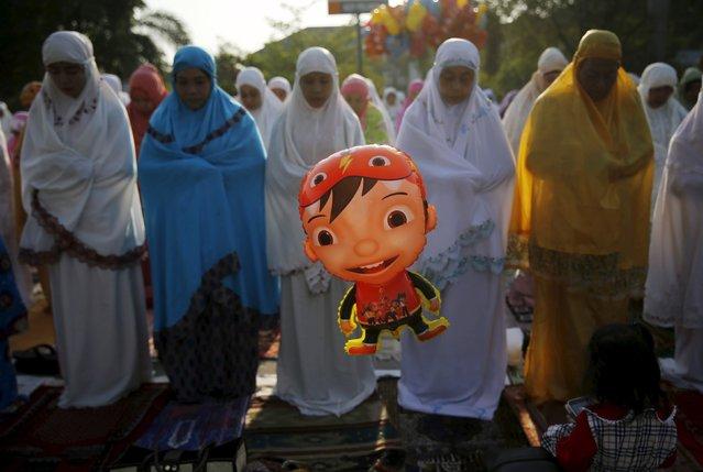 A balloon is seen as Muslim women attend an Eid al-Adha mass prayer at Sunda Kelapa port in Jakarta September 24, 2015. (Photo by Reuters/Beawiharta)