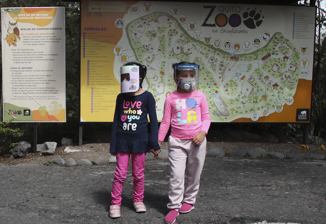Girls wearing face shields as a preventive measure against the new coronavirus wait for their parents to enter the zoo on the outskirts of Quito, in Guayllabamba, Ecuador, Wednesday, July 8, 2020. The zoo is reopening but with strict new social distancing protocols for visitors due to the COVID-19 pandemic. (Photo by Dolores Ochoa/AP Photo)
