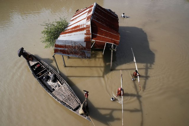 Fishermen wade through the water with their fishing nets in a flooded area in Jamalpur, Bangladesh, July 18, 2020. (Photo by Mohammad Ponir Hossain/Reuters)