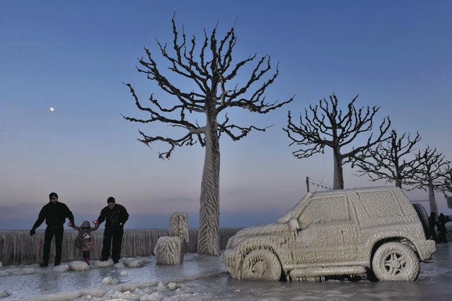 In this February 5, 2012 file photo, people walk along an icy promenade past ice covered cars and trees on the shores of Lake Geneva in Versoix, Switzerland. Across Eastern Europe, thousands of people dug out from heavy snow that had fallen during a cold snap and killed hundreds of people. (Photo by Keystone/Martial Trezzini/AP Photo)