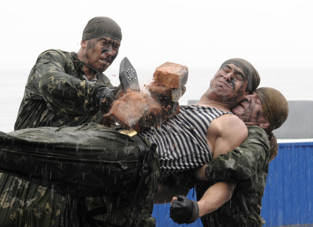 A Russian soldier crushes a pile of bricks with a hammer on the stomach of a fellow soldier during a performance as part of a naval parade rehearsal at the harbor of Russia's far eastern city of Vladivostok, July 23, 2010. (Photo by Yuri Maltsev/Reuters)