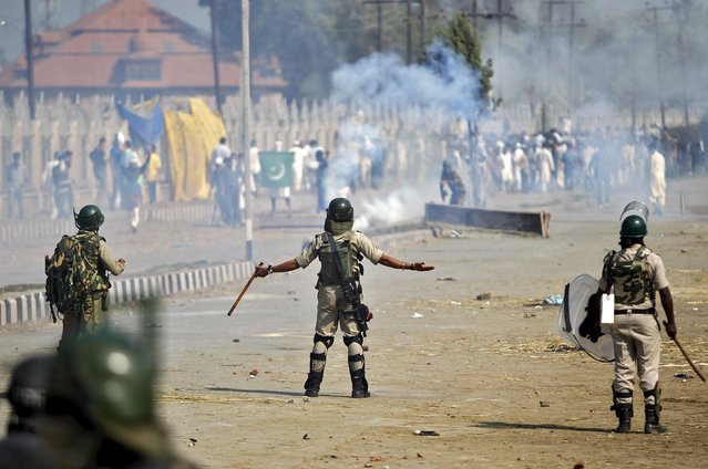 An Indian policeman gestures towards Kashmiri demonstrators during a protest after Eid al-Adha prayers in Srinagar, September 25, 2015. Hundreds of demonstrators on Friday protested against a beef ban order by a state court in India's Kashmir, local media reported. (Photo by Danish Ismail/Reuters)