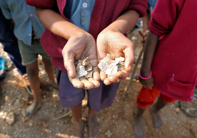 A girl shows some of the mica flakes she has collected whilst working in a open cast illegal mine in Giridih district in the eastern state of Jharkhand, India, January 22, 2016. (Photo by Nita Bhalla/Reuters)