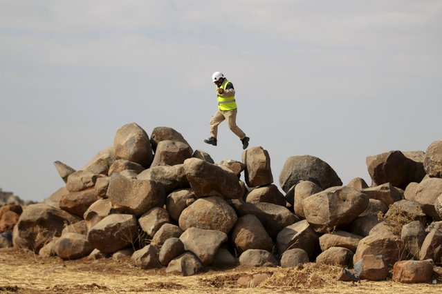 A civil defence member jumps on rocks at a location to get better coverage for wireless devices in Maasran town, in the southern countryside of Idlib, Syria October 8, 2015. (Photo by Khalil Ashawi/Reuters)