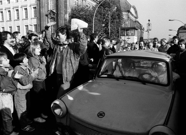 West Berlin citizens welcome East Germans who passed the border checkpoint Invaliden Strasse with an East German Trabant car after the opening of the East German border on November 10, 1989. (Photo by Fabrizio Bensch/Reuters)