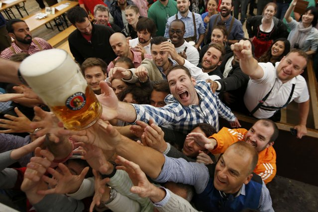 Visitors reach for the one of the first mugs of beer during the opening day of the 183rd Oktoberfest in Munich, Germany, September 17, 2016. (Photo by Michaela Rehle/Reuters)