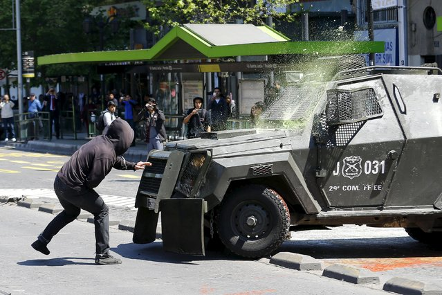 A student protester throws a bottle of paint against a riot police vehicle during a demonstration to demand changes in the education system in Santiago, Chile, October 15, 2015. (Photo by Ivan Alvarado/Reuters)
