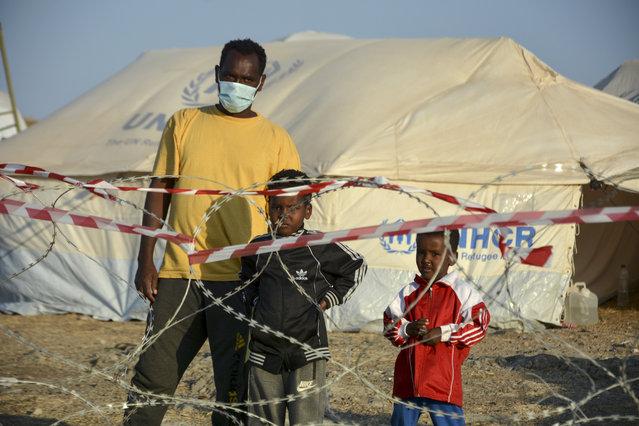 Migrants stand inside the new temporary refugee camp in Kara Tepe, on the northeastern island of Lesbos, Greece, Saturday, September 19, 2020. Police on the Greek island of Lesbos on Friday resumed relocating migrants rendered homeless when fires ravaged the country's largest refugee camp amid a local COVID-19 outbreak. (Photo by Panagiotis Balaskas/AP Photo)