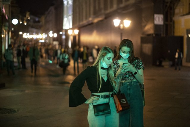 Two women wearing face masks to protect against coronavirus look at a smartphone in the center of Moscow, Russia, Friday, September 25, 2020. Moscow authorities have issued a recommendation for the elderly to stay at home and for employers to allow as many people as possible to work remotely, following a rapid growth of the coronavirus caseload in the Russian capital. (Photo by Alexander Zemlianichenko/AP Photo)