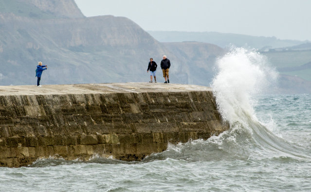 Picture shows a couple about to get a soaking in the stormy weather in Lyme Regis, Dorset, yesterday afternoon September 26th, 2016. Large waves were seen crashing against The Cobb in Lyme Regis yesterday afternoon (Mon) as parts of Britain looks set to see stormy weather this week – with winds of up to 70mph. (Photo by Andrew Sharpe/Geoff Robinson Photography)