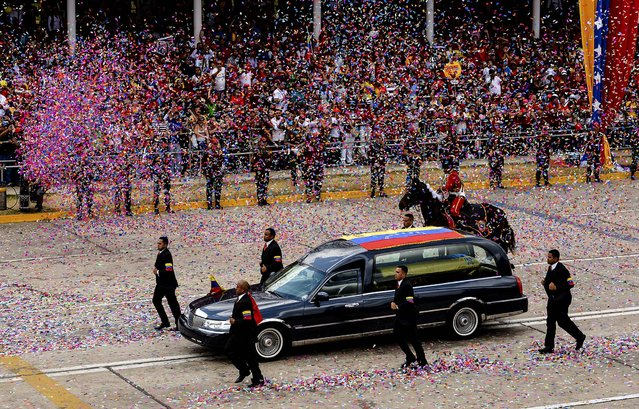 A funeral procession escorts the remains of Hugo Chavez, who died March 5, in Caracas, Venezuela, on March 15, 2013. Chavez's body was taken to its final resting place at the 4F military museum on the outskirts of the 23 de Enero neighborhood. (Photo by Meridith Kohut/The New York Times)