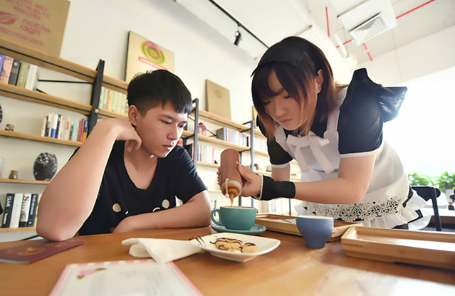 "Pic shows: the maid-themed cafe in Hangzhou; A cafe has been bringing in droves of new customers after hiring young women to dress up in Frech maid costumes while serving diners. Curious coffee- and coffee-lovers are coming from all corners of Hangzhou, capital of East China's Zhejiang Province, to get a taste of the ""maid cafe"" experience. The business is said to have been opened by a man surnamed Yu and his friends, all whom are natives or graduates of the city."