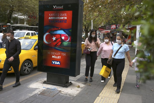 """People wearing masks to help protect against the spread of coronavirus, walk past a billboard that reads """"Turkey and Azerbaijan, two states one nation"""" in Ankara, Turkey, Thursday, October 8, 2020. Turkish President Recep Tayyip Erdogan on Thursday again reiterated his country's full support to Azerbaijan, which he said was determined to reclaim its territory. (Photo by Burhan Ozbilici/AP Photo)"""