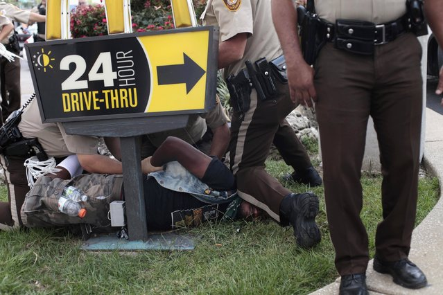 Police officers detain a demonstrator for protesting against the fatal shooting of Michael Brown in Ferguson, Missouri, in this August 18, 2014 file photo. (Photo by Joshua Lott/Reuters)