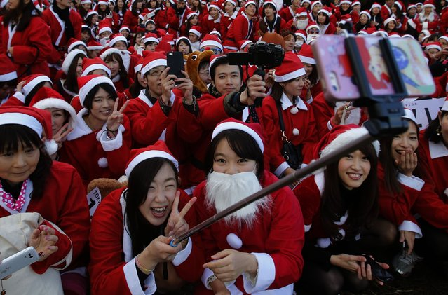 "People dressed in Santa costumes take ""selfies"" during the Tokyo Santa Run at a park in Tokyo December 6, 2014. (Photo by Yuya Shino/Reuters)"