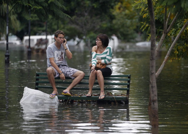 Residents sit on a bench at a flooded public square after a rainstorm in Buenos Aires April 2, 2013. Thunderstorms damaged property and vehicles, cut power and caused delays on flights in Buenos Aires and its suburbs. The City's SAME emergency service announced that the death toll has risen to five. (Photo by Enrique Marcarian/Reuters)