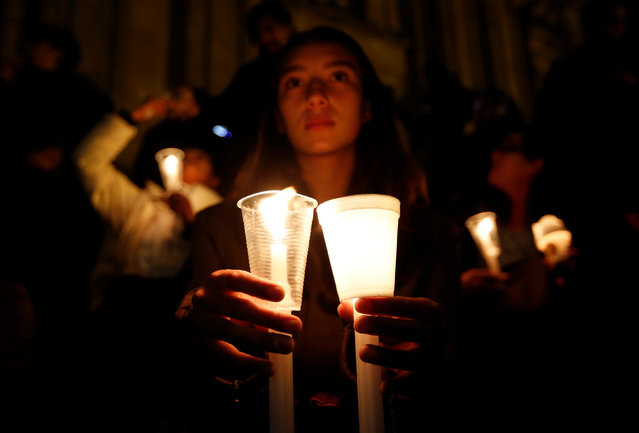 """A supporter of the peace deal signed between the government and the Revolutionary Armed Forces of Colombia (FARC) rebels holds candles while attending a gathering at Bolivar Square during a """"Silent March"""" in Bogota, Colombia, October 5, 2016. (Photo by John Vizcaino/Reuters)"""