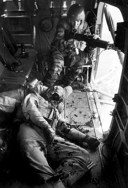 """Farley, unable to leave his gun position until YP13 is out of enemy range, stares in shock at YP3's co-pilot, Lieutenant Magel, on the floor"". (Photo by Larry Burrows/Time & Life Pictures)"