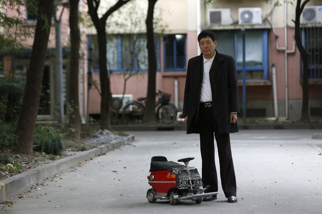 Xu Zhiyun, 60, poses with his home-made motorised mini-vehicle at a street in Shanghai December 9, 2014. Xu spent over two years to complete the mini-vehicle measuring 60cm (24 inches) by 35cm (14 inches) by 40cm (16 inches), which has a 77cc engine and five gear ranges. (Photo by Aly Song/Reuters)