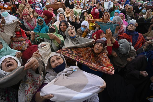 Muslim devotees react as a priest displays a relic believed to be a hair from the beard of Prophet Mohammed during the last Friday of Eid Milad-un-Nabi, which marks the birth anniversary of the Prophet, at the Hazratbal Shrine in Srinagar on November 6, 2020. (Photo by Tauseef Mustafa/AFP Photo)