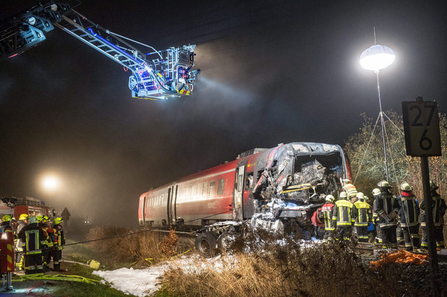Emergency services  inspect a damaged train in Freihung, Germany, 05 November 2015. A passenger train struck a heavy lorry at a rail crossing late 05 November in southern Germany, leaving at least one person dead and multiple injured, police said. The lorry was believed to have stopped in the crossing before the collision, which was followed by an explosion. (Photo by Armin Weigel/EPA)