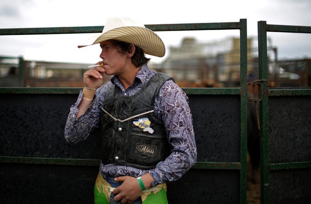 Bull rider Tom Phibbs, 21, from Chiltern, smokes a cigarette before competing at the Deni Ute Muster in Deniliquin, New South Wales, September 30, 2016. (Photo by Jason Reed/Reuters)