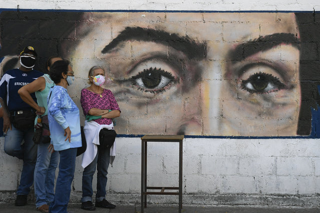 People wearing masks to curb the spread of COVID-19 wait to vote in front of a mural of the eyes of Venezuelan independence hero Simon Bolivar during a voting rehearsal at a public school in the Catia neighborhood of Caracas, Venezuela, Sunday, October 25, 2020. Venezuela's electoral authority is testing the voting process in preparation for the Dec. 6 parliamentary elections. (Photo by Matias Delacroix/AP Photo)
