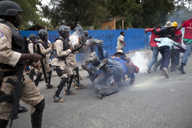 Anti-government demonstrators fall to the ground during clashes with national police officers during a protest calling for the resignation of Haiti's President Michel Martelly in Port-au-Prince, Haiti, Tuesday, December 16, 2014. Haiti's capital has endured a growing number of demonstrations in recent weeks during which protesters have demanded the holding of elections that were expected in 2011 and the resignations of Prime Minister Laurent Lamothe as well as President Michel Martelly. (Photo by Dieu Nalio Chery/AP Photo)
