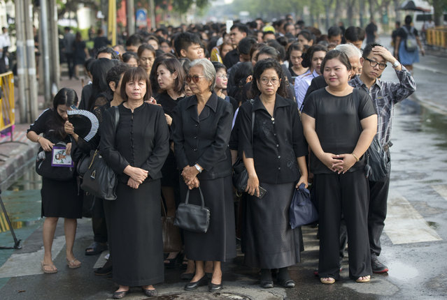 Thai people stand in lines to offer condolences for Thai King Bhumibol Adulyadej at Grand Palace in Bangkok, Thailand, Friday, October 14, 2016. Grieving Thais went to work dressed mostly in black Friday morning, just hours after the palace announced the death of their beloved King Bhumibol, the politically fractious country's unifying figure and the world's longest-reigning monarch.(Photo by Gemunu Amarasinghe/AP Photo)
