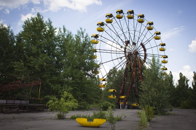 This June 8, 2011 photo shows a Ferris wheel at a playground in the deserted town of Pripyat, Ukraine, some 3 kilometers (1.86 miles) from the Chernobyl nuclear plant. Chernobyl and Fukushima are some 5,000 miles apart but have much in common. The towns nearest to each of these stricken nuclear power stations, in Ukraine and Japan, whose disasters struck 25 years apart, already reveal eerie similarities. (Photo by Sergey Ponomarev/AP Photo)