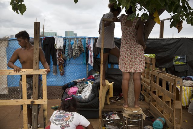 In this Monday, August 24, 2015 photo, 18-year-old Roy Kalama, left, gets help from friends as he tries to build a makeshift tent using pallets at a homeless encampment in the Kakaako district of Honolulu. The camp, one of the nation's largest homeless encampment and once home to hundreds of people, was recently cleared by Hawaii officials. (Photo by Jae C. Hong/AP Photo)